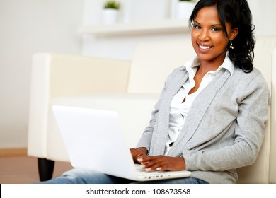Portrait of a lovely girl smiling and looking to you while is sitting on floor in front of her laptop