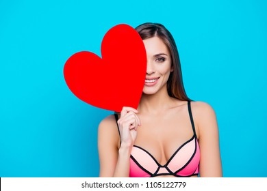 Portrait of lovely girl in swim wear cover half face with big red carton heart figure in hand looking at camera isolated over blue background, celebrating holiday