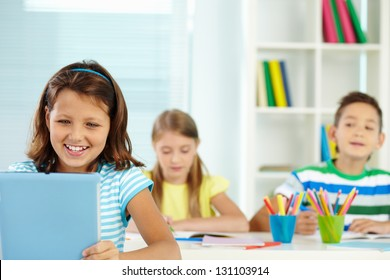 Portrait of lovely girl at workplace looking at digital tablet with classmates on background