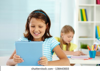 Portrait of lovely girl at workplace looking at digital tablet with classmate on background