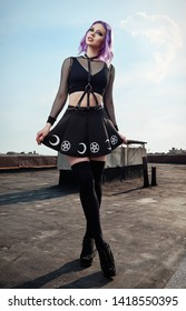 Portrait of lovely gothic girl on the roof. Pastel goth with violet (pink) hair in black clothes