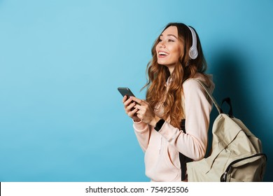 Portrait of a lovely happy girl student with backpack listening to music with headphones while standing and holding mobile phone isolated over blue background