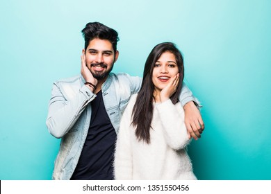 Portrait of lovely indian couple smiling and posing on camera while pleasend signs together over green background