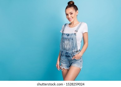 Portrait of lovely lady looking with beaming smile wearing white t-shirt denim jeans shorts isolated over blue background