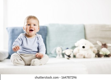 Portrait of lovely laughing baby boy with blue eyes and blue shirt sitting on couch and looking up, blurred toys in background.