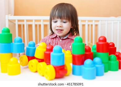 Portrait of lovely little boy playing plastic blocks at home