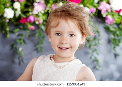 Portrait of the lovely little girl with  flowers. Looking at camera