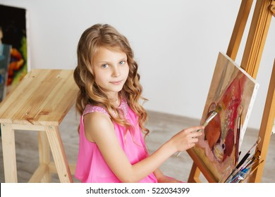 Portrait of a lovely little girl painting a picture in a studio or art school. Creative pensive painter child paints a colorful picture on canvas with oil colors in workshop. Talented kids