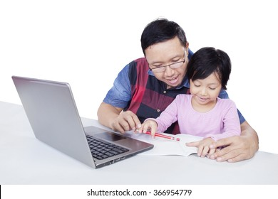 Portrait of lovely little girl studying with her dad, using a book and laptop on the table, isolated on white background