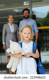 Portrait of lovely little schoolgirl with a teddy bear and her smiling parents in background