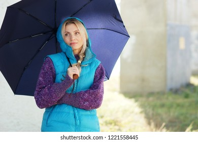 Portrait of lovely mature blond woman with umbrella in the street. Deadpan style portrait.