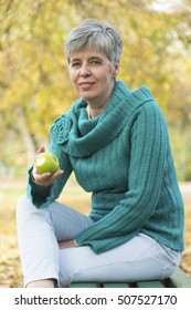 Portrait of lovely middle aged woman in the autumn park eating an apple