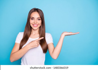 Portrait of lovely millennial holding hand pointing to ads with her index finger isolated over blue background