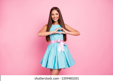 Portrait of lovely model cute teenager teen showing affection attracting boys males men making heart with fingers isolated dressed in bright clothing on rose-colored background