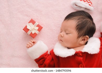 Portrait lovely newborn in red dress with gift box sleeping on mat,happy Christmas celebration time concept.