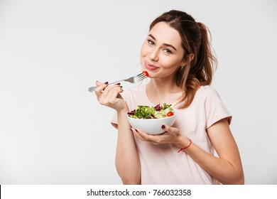 Portrait of a lovely pretty girl eating fresh salad from a bowl isolated over white background