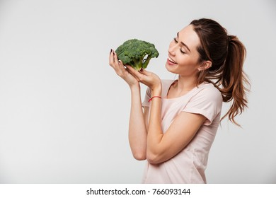 Portrait of a lovely pretty girl holding broccoli isolated over white background