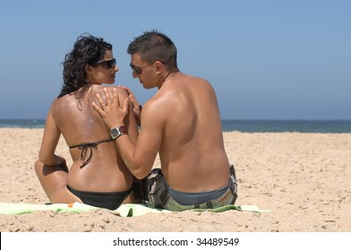 Portrait of a lovely romantic couple applying suncream on the beach