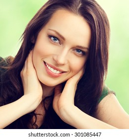 Portrait of lovely smiling young brunette woman, outdoor