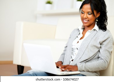Portrait of a lovely student girl smiling and looking to laptop screen at home indoor