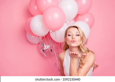 Portrait of lovely sweet chick having many air balloons blowing kiss with pout lips palm to the camera isolated on pink background. Affection inspiration harmony concept