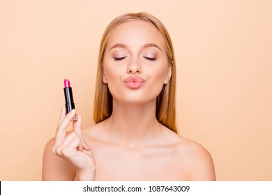 Portrait of lovely, sweet, dreamy girlfriend with close eyes sending air kiss with pout lips having pink pomade in hand isolated on beige background perfection, wellbeing concept