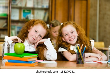 Portrait of lovely twins girls with schoolgirl on background. looking at camera