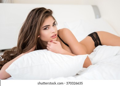 Portrait of a lovely woman in lingerie lying on the bed and looking at camera