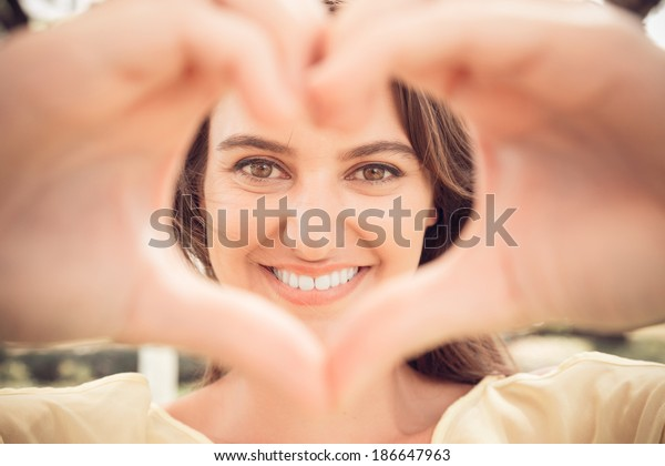 Portrait of a lovely woman making heart of fingers