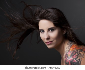 Portrait of a lovely woman with a tatto on the shoulder against a grey background and spread hair