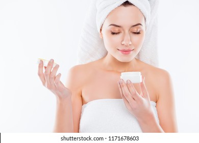 Portrait of lovely woman in towel and turban on head, holding cream for problem combined face skin enjoying smell with close eyes isolated on white background