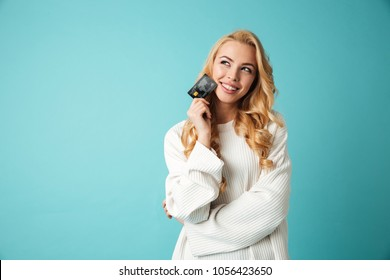 Portrait of a lovely young blonde woman in sweater showing credit card and looking away at copy space isolated over blue background
