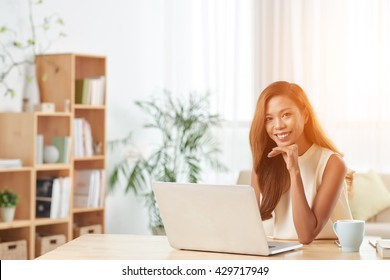 Portrait of lovely young business lady working on laptop in office