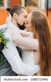 Portrait of a lovely young couple kissing each other in the yard against the backdrop of an orange building.