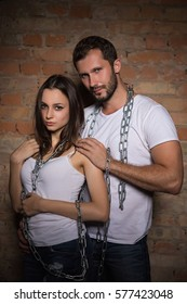 Portrait of lovely young couple posing with chains near brick wall