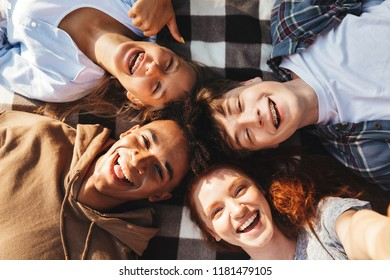 Portrait of lovely young friends guys and girls laughing and lying on blanket in circle outdoor