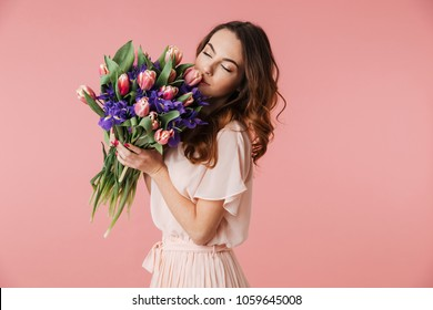 Portrait of a lovely young girl in dress holding big bouquet of irises and tulips isolated over pink background