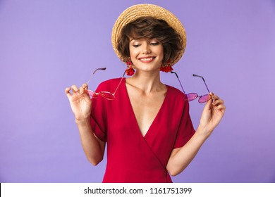 Portrait of a lovely young girl in straw hat holding two pairs of sunglasses isolated violet background