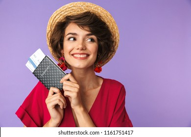 Portrait of a lovely young girl in straw hat holding passport with flying tickets isolated violet background