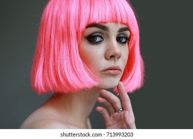portrait of a lovely young girl in a wig with pink  hair