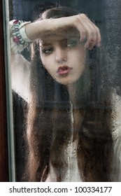 Portrait of a lovely young lady looking through glass window - Indoor in a dark cloudy day, she looks down at right and her head is resting on the right arm
