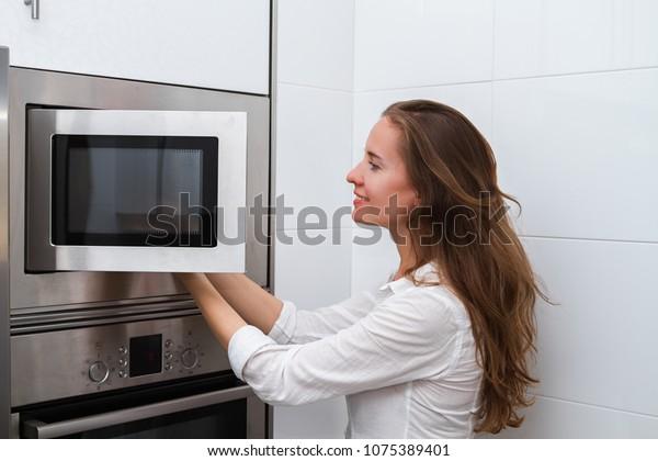 Portrait of a lovely young modern woman cooking in the microwave oven.