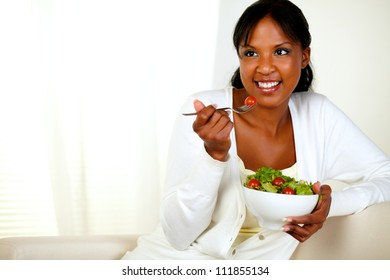 Portrait of a lovely young woman enjoying fresh vegetable salad. With copyspace.