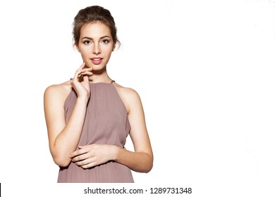 Portrait of lovely young woman with prefect natural makeup in stylish beige dress. Beauty and happiness concept. Copy space in right side. Isolated on grey background