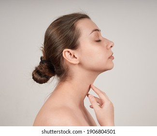 Portrait of lovely young woman in profile with bare shoulders, touching her neck. Studio shot on light background