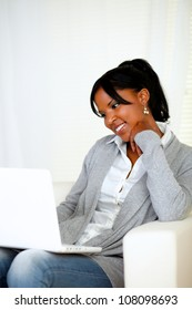 Portrait of a lovely young woman smiling and looking to laptop screen at home indoor