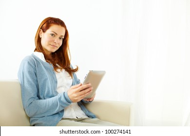 Portrait of a lovely young woman using a tablet PC