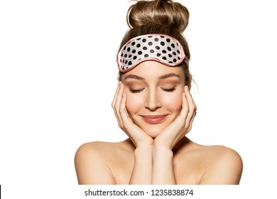 Portrait of lovely young woman wearing sleeping mask and kindly smiling. Beauty and skincare concept. Naturally beautiful girl posing on white background