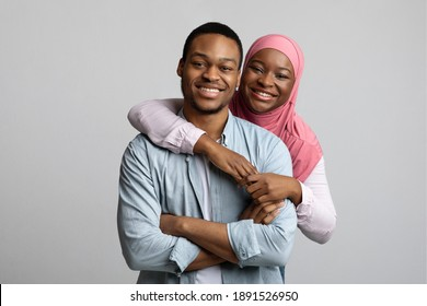 Portrait of loving african american young muslim couple posing on grey studio background. Beautiful black man and woman in hijab hugging and smiling at camera, relationships concept