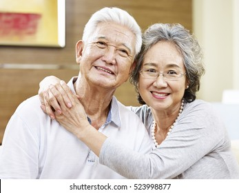 portrait of a loving asian couple, looking at camera smiling